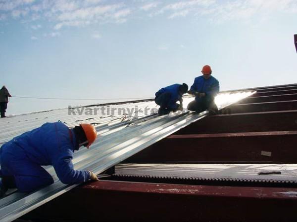 Рабочие укладывают профнастил на крышу