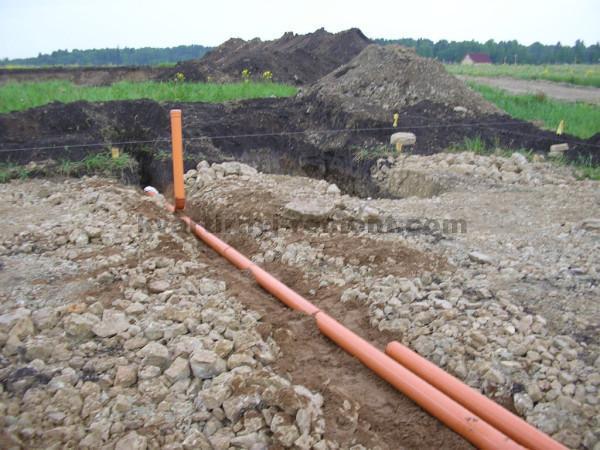 На фото – Укладка канализационных труб.