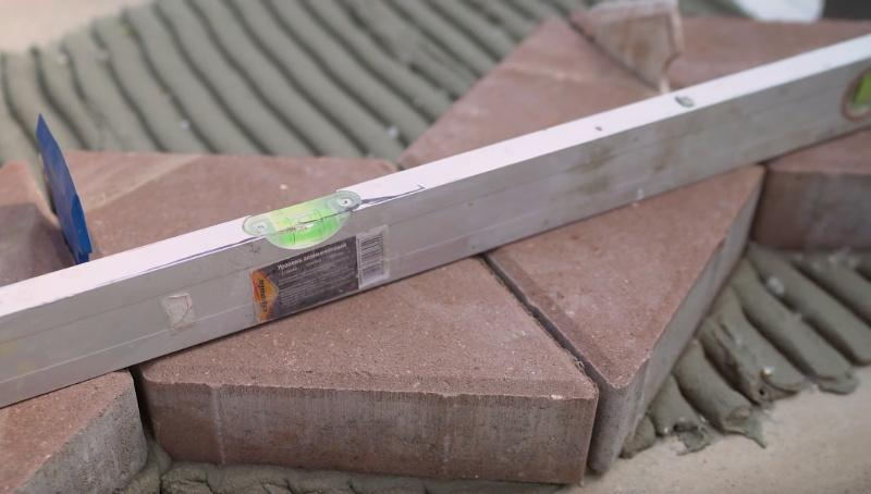 При помощи строительного уровня подгоняем брусчатку